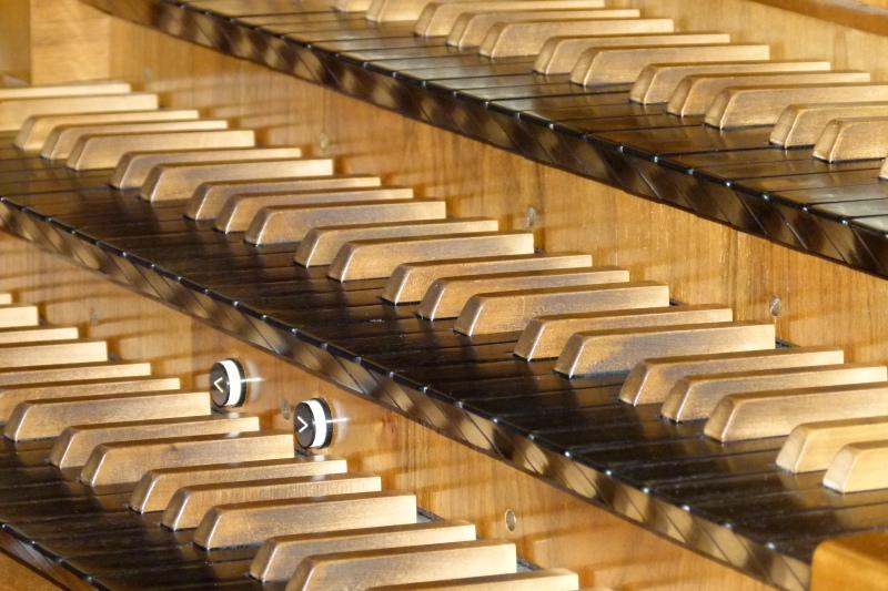 Orgel spielen auf den Manualen einer Pfeifenorgel.
