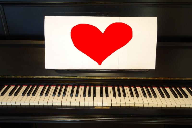 Klavier mit rotem Herz auf Notenblatt